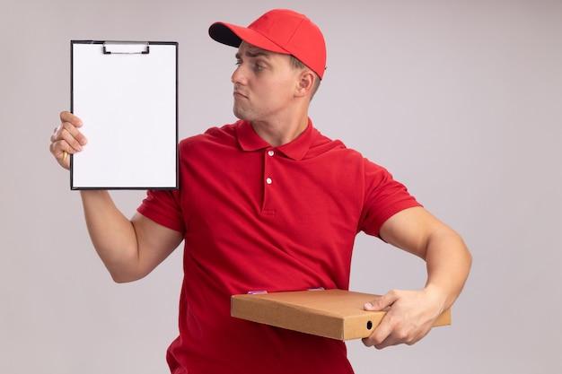 Beeindruckter junger lieferbote, der uniform mit kappe hält, die pizzaschachtel hält und klemmbrett in seiner hand lokalisiert auf weißer wand betrachtet