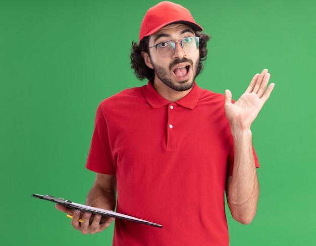 Beeindruckter junger liefermann in roter uniform und mütze mit brille, die zwischenablage und bleistift hält und nach vorne schaut und leere hand isoliert auf grüner wand zeigt