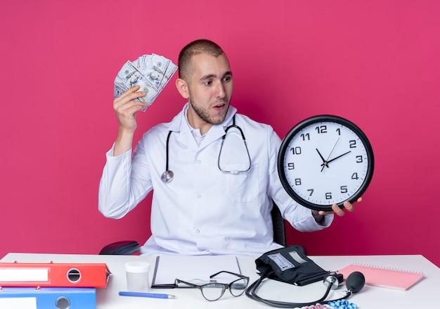 Beeindruckter junger männlicher arzt, der medizinische robe und stethoskop trägt, die am schreibtisch mit arbeitswerkzeugen sitzen, die uhr und geld halten, die auf rosa lokalisiert betrachten