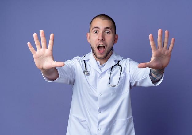 Beeindruckter junger männlicher arzt, der medizinische robe und stethoskop um seinen hals trägt und hände ausstreckt, die auf purpur gestikulieren