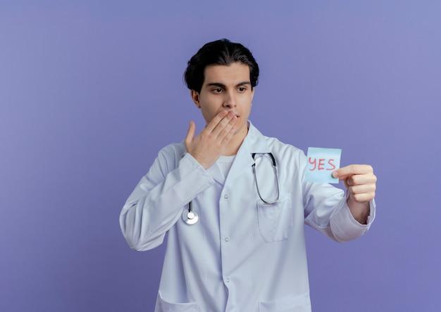 Beeindruckter junger männlicher arzt, der medizinisches gewand und stethoskop trägt, die ja-hinweis zeigt, der sie betrachtet, die hand auf mund lokalisiert auf lila wand mit kopienraum hält