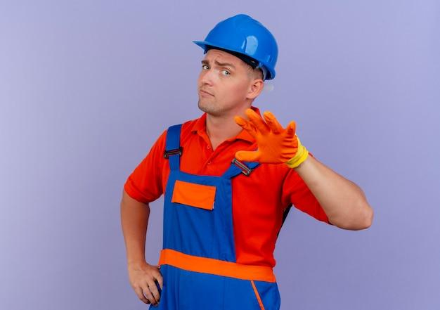 Beeindruckter junger männlicher baumeister, der uniform und schutzhelm in handschuhen trägt, die hand ausstrecken