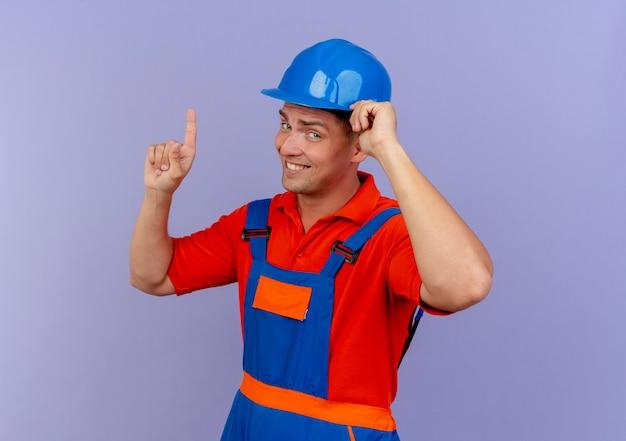 Beeindruckter junger männlicher baumeister, der uniform- und schutzhelm trägt, hand auf helm setzt und nach oben zeigt