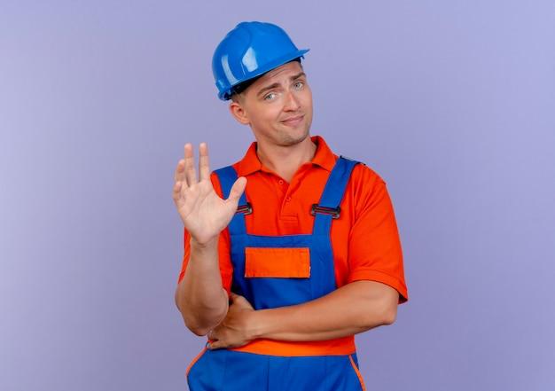 Beeindruckter junger männlicher baumeister, der uniform und schutzhelm trägt hand hebt