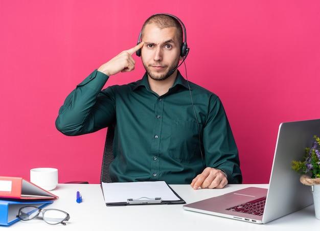 Beeindruckter junger männlicher callcenter-betreiber mit headset am schreibtisch sitzend mit bürowerkzeugen, die den finger auf die schläfe legen