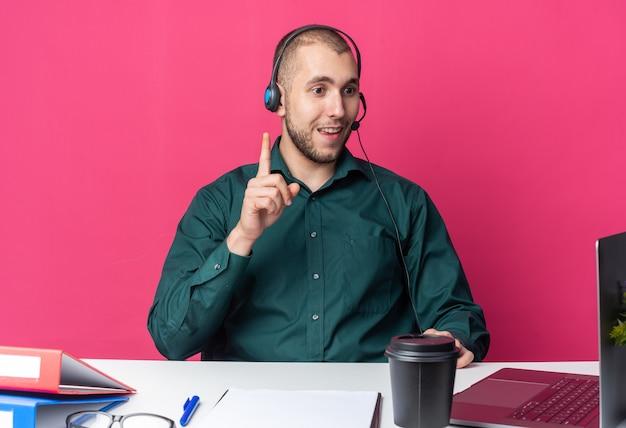 Beeindruckter junger männlicher callcenter-betreiber mit headset am schreibtisch sitzend mit bürowerkzeugen, die laptop-punkte nach oben betrachten