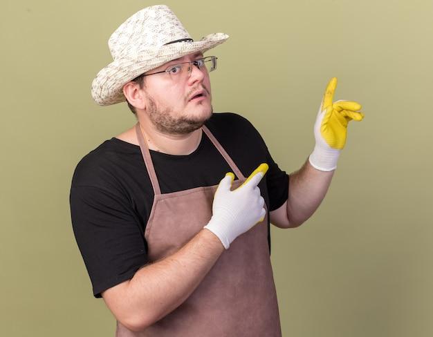 Beeindruckter junger männlicher gärtner mit gartenhut und handschuhen zeigt mit den fingern hinten isoliert auf olivgrüner wand mit kopierraum