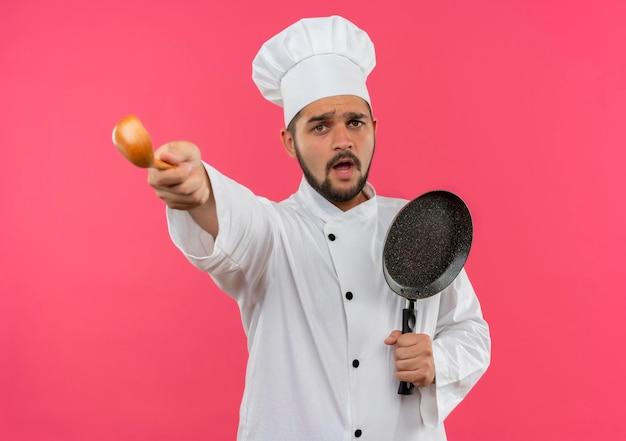 Beeindruckter junger männlicher koch in kochuniform, der bratpfanne hält und löffel isoliert auf rosa wand ausstreckt