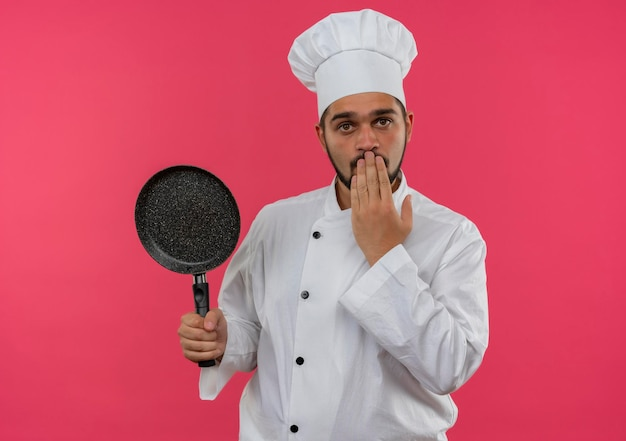 Beeindruckter junger männlicher koch in kochuniform, der eine bratpfanne hält und die hand auf den mund legt, isoliert auf rosa wand