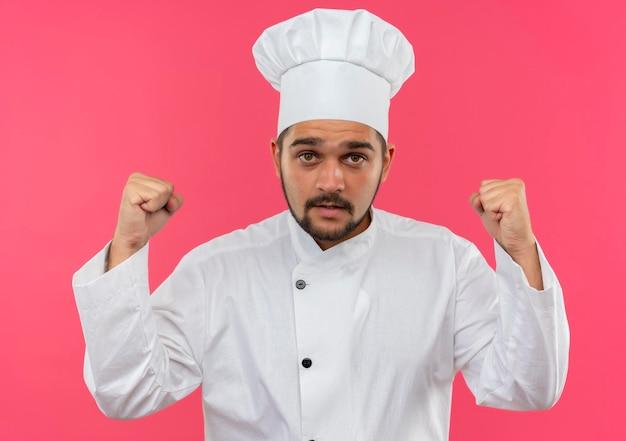 Beeindruckter junger männlicher koch in kochuniform, der fäuste hebt und auf rosa wand isoliert
