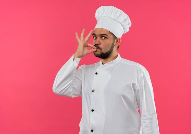 Beeindruckter junger männlicher koch in kochuniform, der leckere geste isoliert auf rosa wand mit kopierraum macht