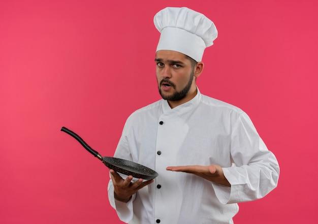 Beeindruckter junger männlicher koch in kochuniform, der mit der hand auf die bratpfanne einzeln auf rosafarbener wand zeigt und zeigt