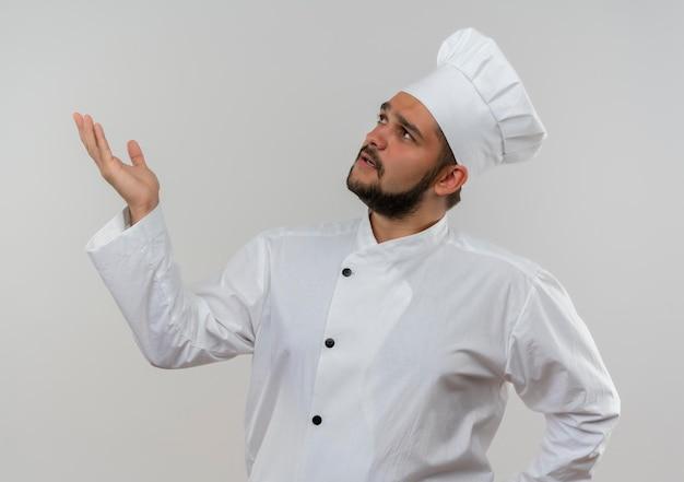 Beeindruckter junger männlicher koch in kochuniform, der nach oben schaut und leere hand isoliert auf weißer wand zeigt
