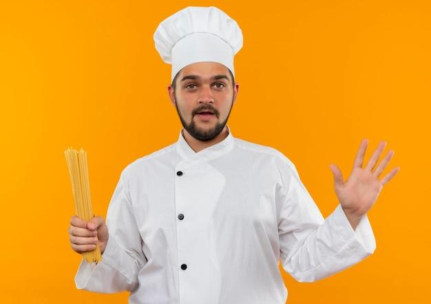 Beeindruckter junger männlicher koch in kochuniform, der spaghetti-nudeln hält und leere hand isoliert auf oranger wand zeigt