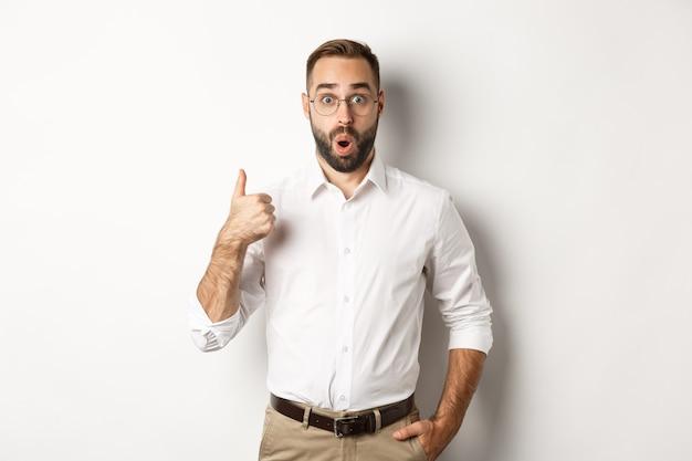 Beeindruckter junger männlicher unternehmer, der daumen hoch zeigt, etwas gutes lobt, wie und zustimmt, weiß