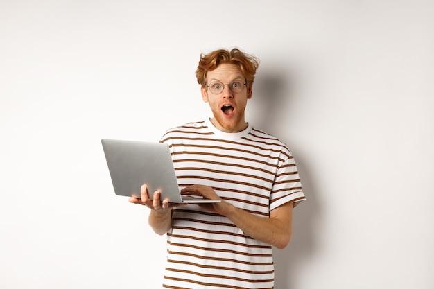 Beeindruckter junger mann, der laptop in händen hält, kamera mit aufgeregtem gesicht anstarrt, online-werbung auf der website liest und gegen weißen hintergrund steht.