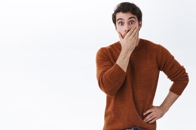 Beeindruckter junger mann hört frischen klatsch, kann seine wahren, starren augen nicht fassen