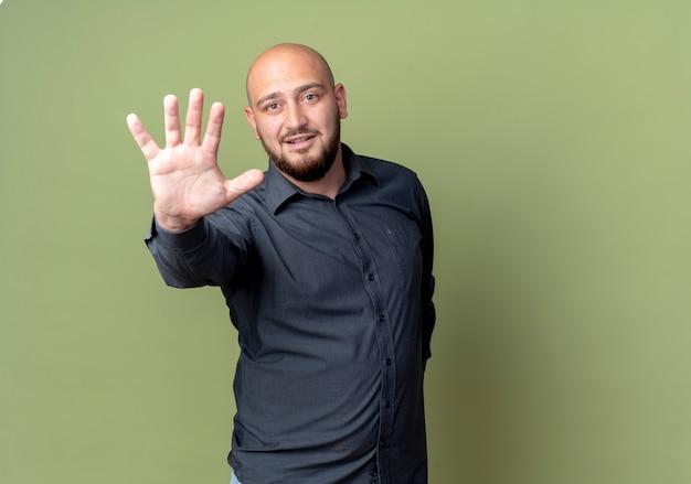 Beeindruckter junger mann mit kahlem callcenter, der die hand ausstreckt und fünf auf olivgrün mit kopierraum isoliert zeigt