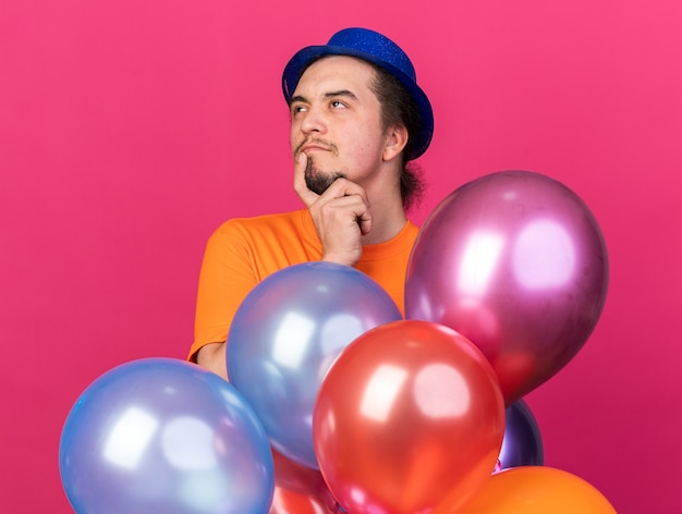 Beeindruckter junger mann mit partyhut, der hinter ballons steht und finger auf kinn legt