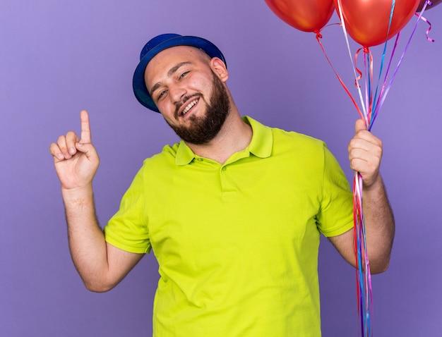 Beeindruckter junger mann mit partyhut, der luftballons hält, zeigt nach oben isoliert auf blauer wand