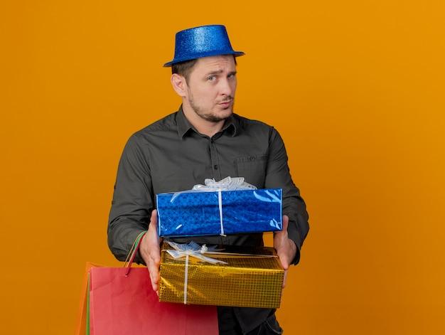 Beeindruckter junger party-typ, der blauen hut trägt, der geschenktüte mit den auf orange isolierten kisten heraushält