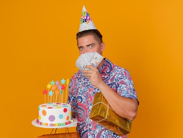 Beeindruckter junger party-typ, der geburtstagskappe hält, die geschenke mit kuchen und bedecktem gesicht mit bargeld lokalisiert auf orange hält