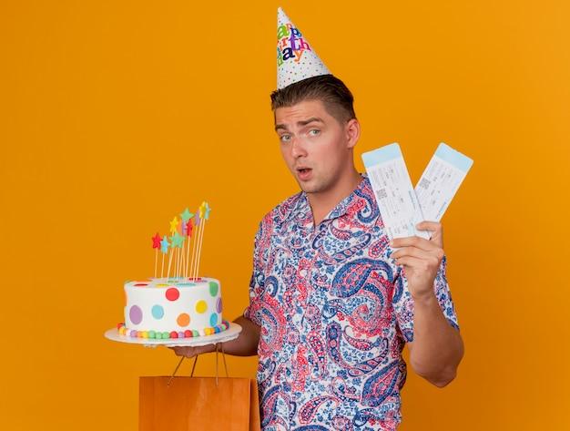 Beeindruckter junger party-typ, der geburtstagskappe mit geschenktüte mit kuchen und tickets trägt, die auf orange isoliert werden