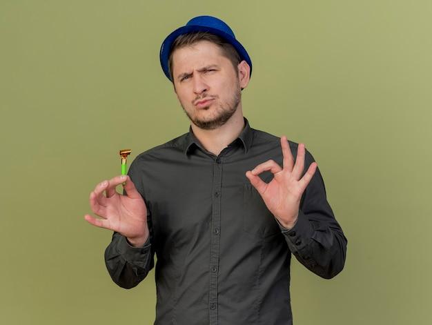 Beeindruckter junger party-typ, der schwarzes hemd und blauen hut hält, der partygebläse hält, das okey geste lokalisiert auf olivgrün zeigt