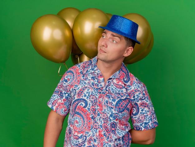 Beeindruckter junger party-typ, der seite betrachtet, die blauen hut trägt, der vor ballons lokalisiert auf grünem hintergrund steht