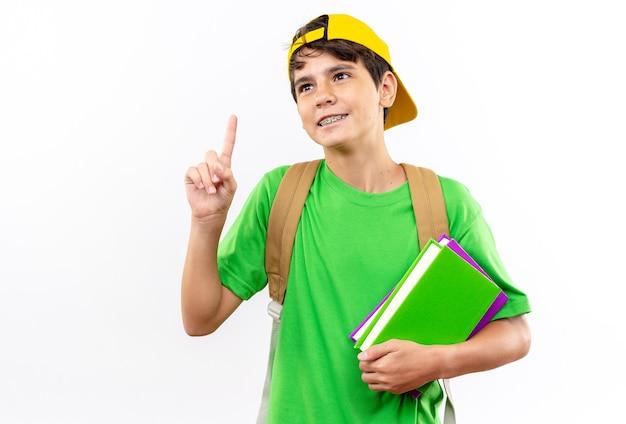 Beeindruckter junger schuljunge, der einen rucksack mit einer kappe trägt, die bücher nach oben hält?