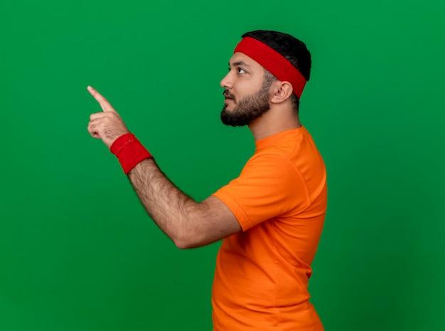 Beeindruckter junger sportlicher mann, der seite betrachtet, die stirnband und armbandpunkte an der seite trägt