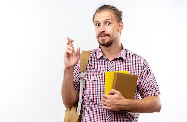 Beeindruckter junger student mit rucksack, der bücher hält, die die finger einzeln auf weißer wand kreuzen