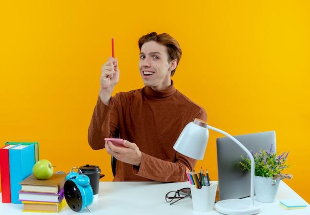Beeindruckter junger studentenjunge, der am schreibtisch mit schulwerkzeugen sitzt, die notizbuch halten und stift anheben