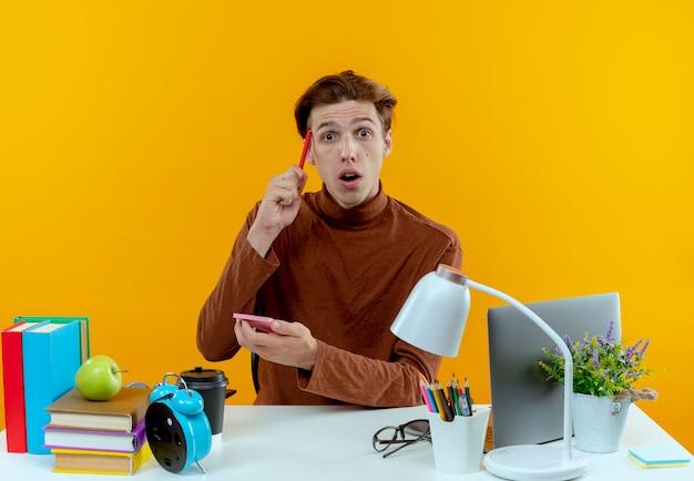 Beeindruckter junger studentjunge, der am schreibtisch mit schulwerkzeugen sitzt, notizbuch hält und stift auf stirn setzt