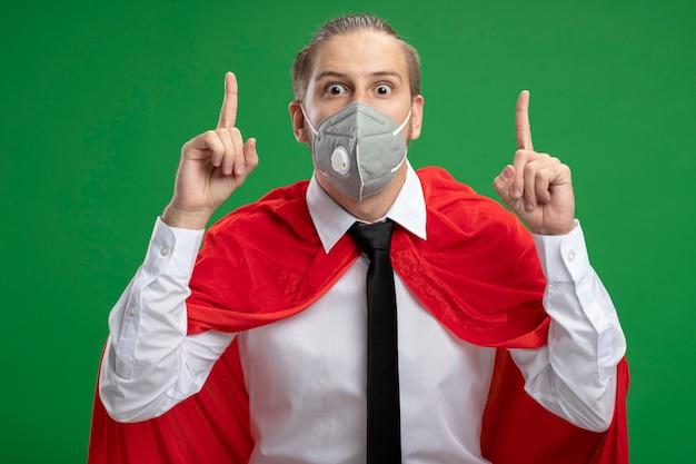 Beeindruckter junger superheld, der medizinische maske und krawattenpunkte oben auf grünem hintergrund trägt