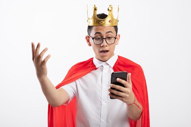 Beeindruckter junger superheldenjunge im roten umhang, der brille und krone hält und handy hält, das hand in luft lokalisiert auf weißem hintergrund hält