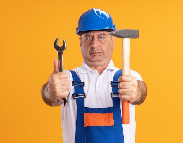 Beeindruckter kaukasischer erwachsener baumeister in uniform hält schraubenschlüssel und hammer auf orange