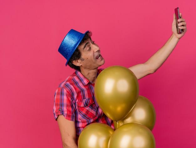 Beeindruckter kaukasischer parteimann mittleren alters, der parteihut trägt, der hinter luftballons steht, die selfie lokalisiert auf purpurrotem hintergrund mit kopienraum nehmen