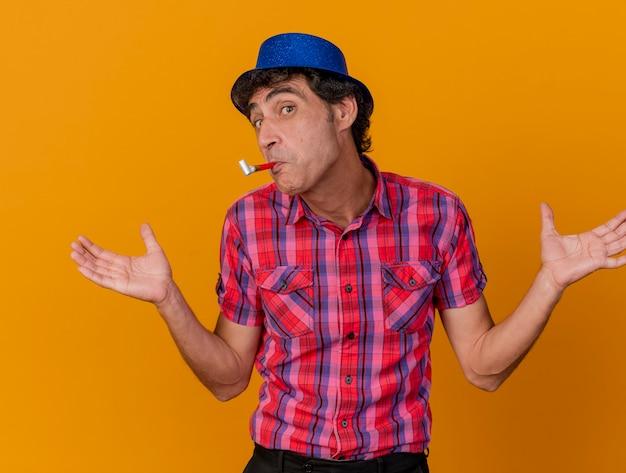 Beeindruckter kaukasischer party-mann mittleren alters, der partyhut betrachtet kamera, die leere hände mit partygebläse im mund lokalisiert auf orange hintergrund zeigt