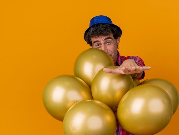 Beeindruckter kaukasischer party-mann mittleren alters, der partyhut trägt, der hinter luftballons steht, streckt hand in richtung lokalisiert auf orange wand mit kopienraum aus