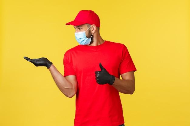 Beeindruckter kurier, angestellter in roter uniform und medizinischer maske, daumen hoch als blick auf seine hand