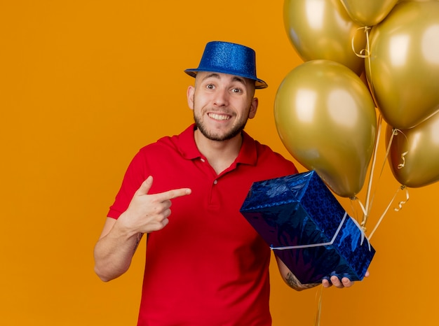 Beeindruckter lächelnder junger hübscher slawischer party-typ, der partyhut hält, der luftballons und geschenkverpackung betrachtet kamera betrachtet, die auf geschenkverpackung lokalisiert auf orange hintergrund zeigt