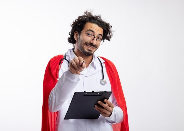 Beeindruckter lächelnder junger kaukasischer superheldenmann in der optischen brille, die arztuniform mit rotem umhang und mit stethoskop um hals trägt, hält klemmbrett und zeigt mit bleistift