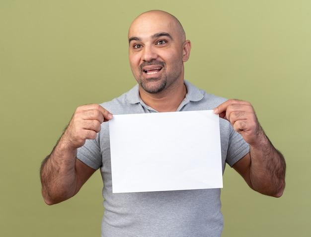 Beeindruckter lässiger mann mittleren alters, der leeres papier hält und die seite isoliert auf olivgrüner wand betrachtet