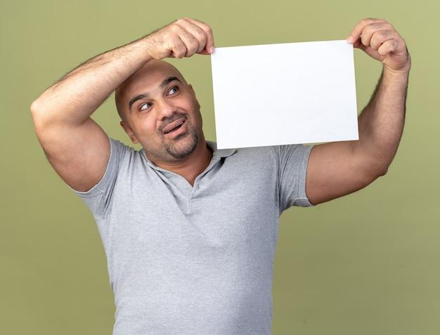Beeindruckter lässiger mann mittleren alters, der leeres papier in der nähe des kopfes hält und es isoliert auf olivgrüner wand betrachtet
