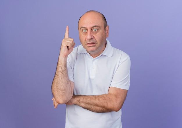 Beeindruckter lässiger reifer geschäftsmann, der hand unter ellbogen legt und finger lokalisiert auf lila hintergrund mit kopienraum anhebt