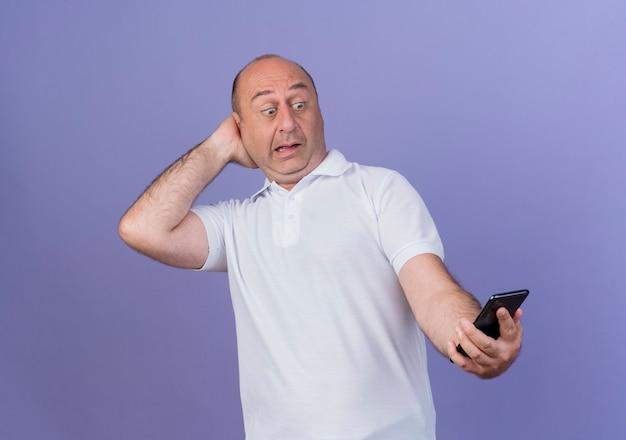 Beeindruckter lässiger reifer geschäftsmann, der handy hält und betrachtet und hand hinter kopf lokalisiert auf lila hintergrund setzt