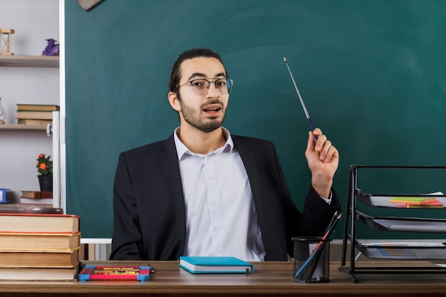 Beeindruckter männlicher lehrer, der eine brille trägt, zeigt mit einem zeigerstab an der tafel, die am tisch mit schulwerkzeugen im klassenzimmer sitzt