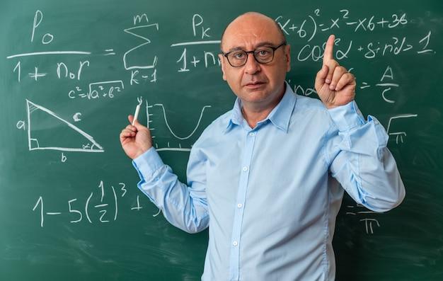 Beeindruckter männlicher lehrer mittleren alters mit brille, der vor der tafel steht und nach oben gestrandet ist