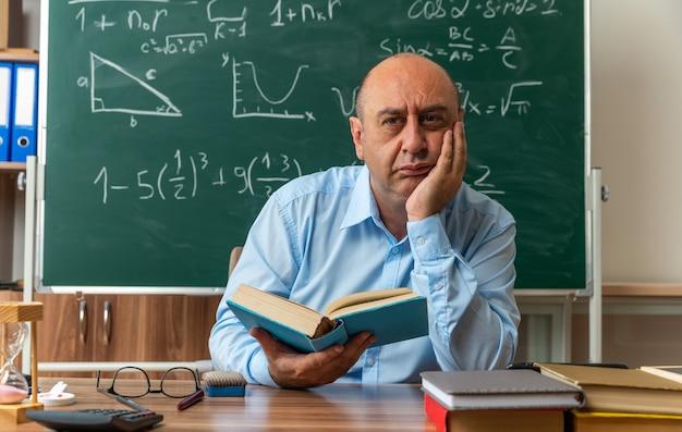 Beeindruckter männlicher lehrer mittleren alters sitzt am tisch mit schulmaterial, das ein buch hält und die hand auf die wange im klassenzimmer legt